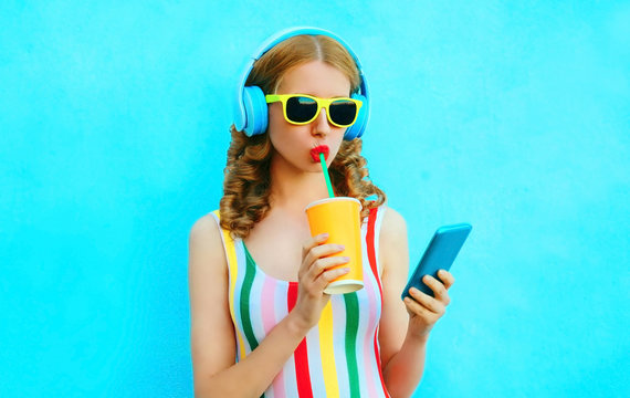 Portrait cool girl drinking fruit juice holding phone listening to music in wireless headphones on colorful blue background