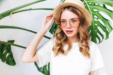 Wall Mural - Close-up portrait of adorable fair-haired woman touching her straw hat with sly smile. Indoor photo of good-looking trendy girl with curly hairstyle posing beside green plant on the wall.