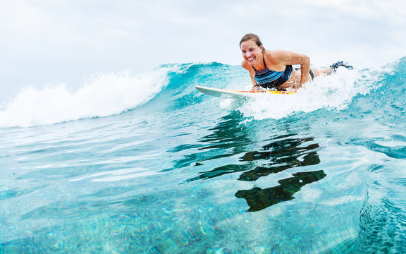 Young woman surfer starts riding the turquoise ocean wave looks at the camera and smiles