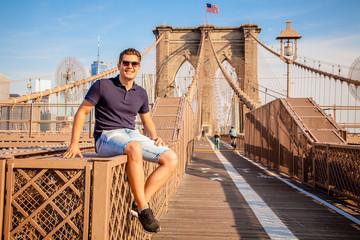Tourist model posing for photo taking on a Brooklyn Bridge