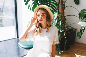 Wall Mural - Thoughtful blonde girl in vintage straw hat posing in front of flowerpot with big green plant. Indoor portrait of pensive curly young woman in white attire and stylish glasses.