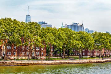 Governors Island and red old retro brick buildings near fort Jay separated from Brooklyn by Buttermilk Channel during sunny summer day in New York City, USA