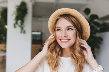 Wall Mural - Dreamy smiling girl with pale skin looking up and touching fair curles. Close-up portrait of fascinating young lady in straw hat posing in room with plants on the light walls.