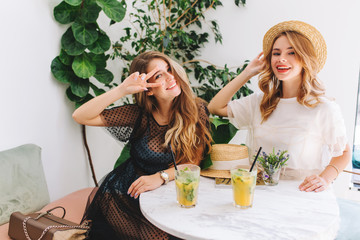 Wall Mural - Long-haired blonde girl in cute wristwatch posing with pleasure near charming friend in white dress. Indoor portrait of elegant young ladies in glamour attires chilling in cafe with cocktails.