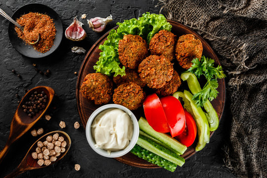 Roasted chickpeas falafel patties with garlic yogurt sauce, served with lettuce and fresh vegetables in a plate over dark stone background. Healthy vegan food, clean eating, dieting, top view