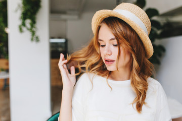 Wall Mural - Close-up portrait of dreamy young lady with curly hairstyle and pale skin wearing elegant straw hat decorated with white ribbon. Indoor photo of cute girl with eyes closed plays with blonde hair.