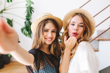 Long-haired girl with sincere smile making selfie while her friend posing with kissing face expression. Close-up portrait of two excited young ladies wearing hats and taking picture in room with plant