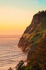 Seaside landscape of rocky cliffs in Oregon at sunset.