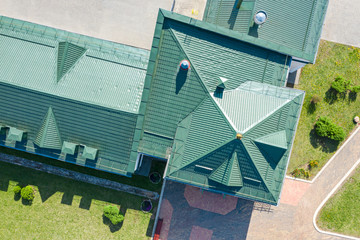 green metal house roof with installed ventilation pipes. aerial view