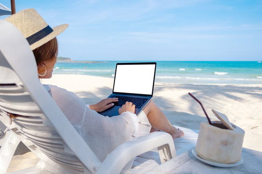 Mockup image of a woman using and typing on laptop computer with blank desktop screen while laying down on beach chair on the beach
