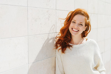 Smiling young woman near white wall