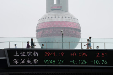 People walk by an electronic board showing the Shanghai and Shenzhen stock indexes, on a pedestrian overpass at Lujiazui financial district in Shanghai