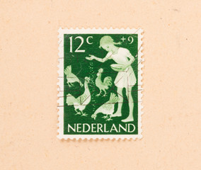 THE NETHERLANDS 1960: A stamp printed in the Netherlands shows a child feeding chickens, circa 1960