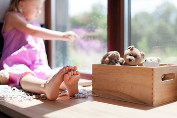 Child is sitting barefoot on window sill at home. Kid is looking out window. Little girl with wooden box of toy teddy bears.