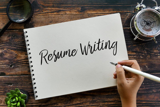 Top view of magnifying glass,clock,plant,pen with hand writing ' Resume Writing ' on a notebook on wooden background,