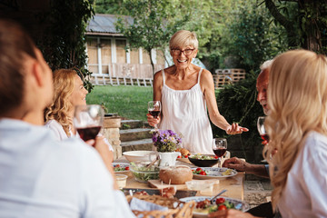 Family eating at the dining table outdoors, celebration
