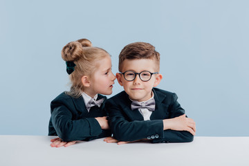 education. little girl little boy whispers to the ear,  sitting at the white table, isolated on blue background, copy space, school concept