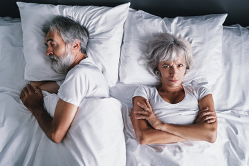 Overhead of senior couple in the bed. Pretty aged woman is angy with her sleeping husband.