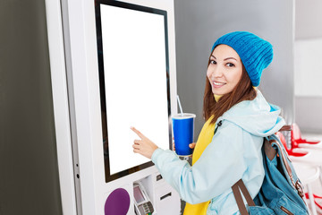 Happy Asian woman orders food in the touch screen terminal with electronic menu in fastfood restaurant. Modern technology concept