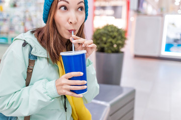 happy woman drinking soda with straw in a mall