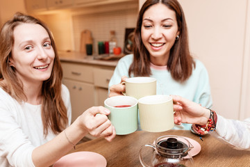 Friends girls communicate laugh and drink tea in the kitchen in their house