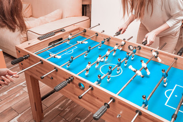 Friends girls take a break and play table football and have fun