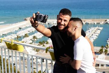 Una pareja gay se hace un selfie en el balcón con el puerto detrás de ellos en un día de verano
