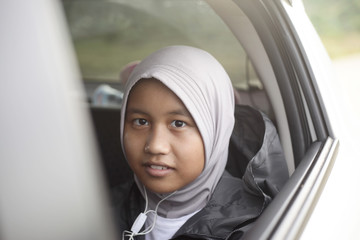 Happy Asian Muslim Girl Listening to Music in the Backseat of a Car