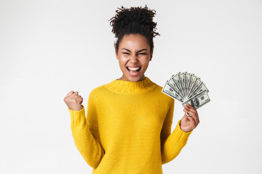 African excited emotional happy woman posing isolated over white wall background holding money.
