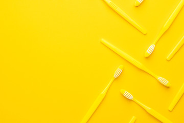 many new plastic yellow toothbrushes in order on the yellow background with copy space