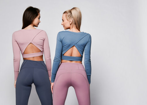Two sporty blonde and brunette girls in athletic body cloth sport wear cloth stand together after workout on gray