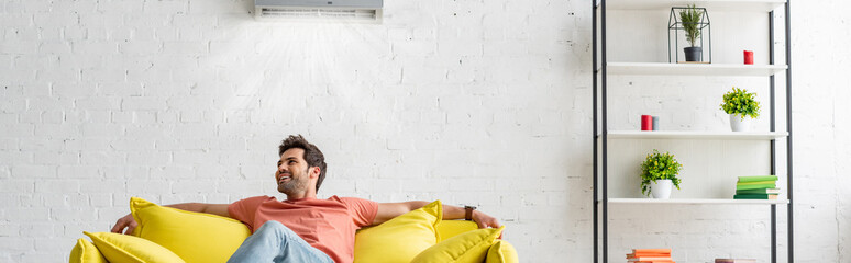 panoramic shot of handsome man sitting on yellow sofa under air conditioner at home Wall mural
