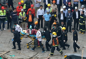 Firefighters carry a casualty on a stretcher at the site where a building collapsed, in Shanghai