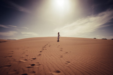 Lonely woman walking free in the dunes desert with white elegant dress enjoying outdoor leisure activity and beautiful place around - travel and lifestyle concept