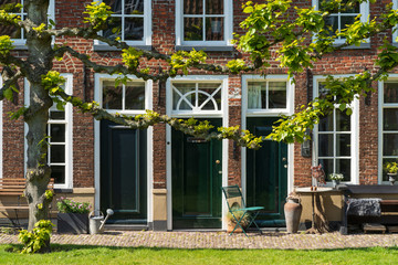 Facade of old almshouse at a small, green courtyard (Sint Anthony Gasthuis) in the Dutch city of Groningen. Netherlands
