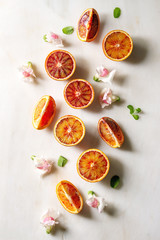 Group of fresh organic Sicilian blood oranges sliced and whole, edible flowers, mint leaves over white marble background. Flat lay, space