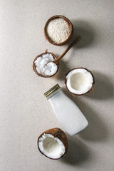Variety of coconut products milk in glass bottle, oil and flakes in shell, fresh broken coconut on grey spotted background. Healthy eating. Flat lay, space