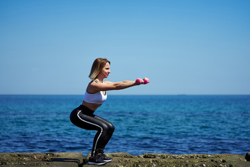Horizontal photo of a woman who does sports exercises on the beach of the ocean or sea. The woman squats and holds dumbbells in her hands.