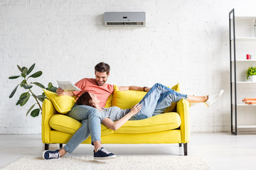 happy man with smiling girlfriend relaxing on yellow sofa under air conditioner at home Fotomurais