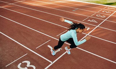 Outdoor horizontal image of young woman athlete running on racetrack at stadium. View from above of sportswoman during running training session for competition. People, sport and healthy lifestyle Wall mural