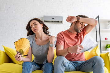 pretty woman with hand fan and handsome man with newspaper suffering from heat at home
