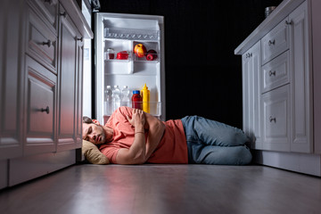 exhausted young man sleeping on kitchen floor near open refrigerator