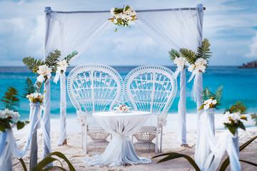 Beach wedding arch gazebo ceremonial decorated with white flowers on a tropical grand anse sand beach. Outdoor beach wedding setup. La Digue, Seychelles
