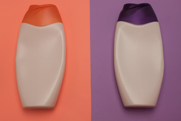 Beauty, decorative cosmetics bottles. Peach and purple colors background, flat lay, top view,...