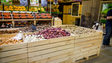 Closeup image of fresh vegetables in wooden boxes on grocery store counters