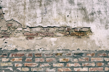 Old damaged brick wall with shabby plaster