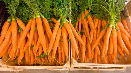 Closeup image of fresh ripe carrots lying in wooden crated on counter at store. Closeup texture or pattern of fresh ripe vegetables. Beautiful food background