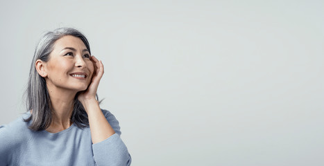 Side profile of charming asian woman smiling on white background