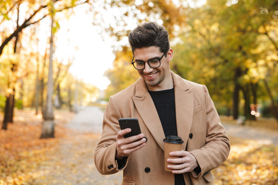 Image of handsome casual man wearing coat using cellphone and smiling n autumn park