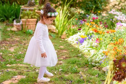 Side view full length portrait of beautiful little girl in white dress having fun a summer garden.